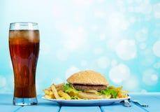 Фраи гамбургера, француза и стеклянная кола на абстрактной голубой предпосылке Стоковое Изображение