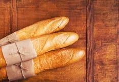 Французские хлебцы на деревенском деревянном столе Стоковые Изображения