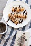 Французские eclairs на белой плите с шоколадом Стоковые Фото