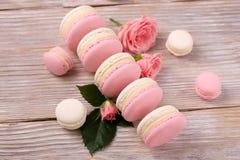 Французские macarons десерта с розовым цветком на деревянной предпосылке Стоковые Фотографии RF