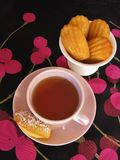Французские madeleines и чашка чаю в винтажной посуде на черноте и пинке вишн-сделали по образцу скатерть Стоковое Изображение RF