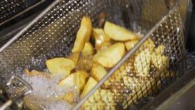 Французский картофель фри глубоко зажарен, кипя масло, поднимает вверх и окунает взгляд настолько вкусный видеоматериал