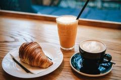 Французский традиционный десерт круассана рядом с капучино кофе и апельсиновым соком в кафе для завтрака Стоковая Фотография