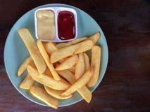 Француз жарит в плите на деревянной таблице с майонезом и томатным соусом Взгляд сверху Стоковое Фото