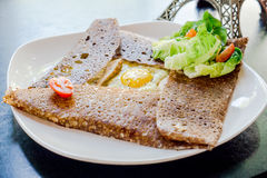 Француз крепирует с куском цыпленка, сыром, яичко на белой плите ест с зеленым салатом и томатом вишни Стоковое Изображение
