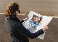 Француз Le Monde женщины читая отжимает семенозачаток избраний Ангелы Меркели Стоковая Фотография