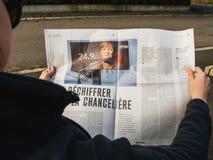 Француз Le Monde женщины читая отжимает семенозачаток избраний Ангелы Меркели Стоковые Изображения