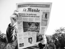 Француз Le Monde женщины читая отжимает семенозачаток избраний Ангелы Меркели Стоковое Фото