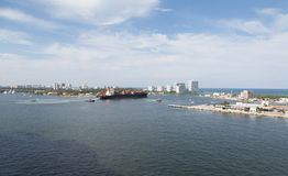 Фрахтовщик и буксиры покидая гавань Стоковые Изображения