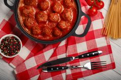 Фрикадельки в томатном соусе со специями в сковороде на белой деревянной доске стоковое изображение rf