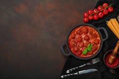 Фрикадельки в томатном соусе со специями, томатами вишни, макаронными изделиями и базиликом в сковороде на ржавой коричневой пред стоковое изображение rf