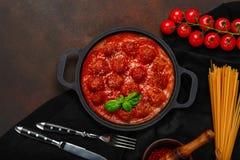 Фрикадельки в томатном соусе со специями, томатами вишни, макаронными изделиями и базиликом в сковороде на ржавой коричневой пред стоковые фотографии rf