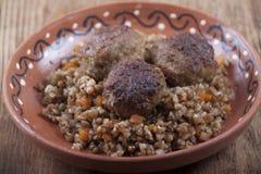 Фрикадельки с кашой гречихи в блюде глины и глине Стоковые Изображения RF