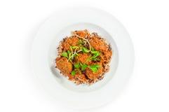 Фрикадельки с коричневым рисом в белой плите изолированной на белизне Стоковые Фото