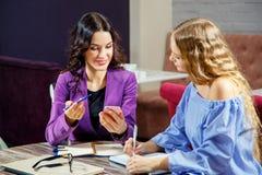 2 фрилансера обсуждают новые проекты пока сидящ в кафе с электронными устройствами Стоковая Фотография