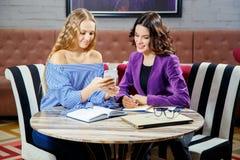 2 фрилансера обсуждают новые проекты пока сидящ в кафе с электронными устройствами Стоковое Изображение