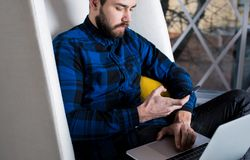 Фрилансер бородатого парня битника успешный используя мобильный телефон и портативный компьютер для работы расстояния стоковое изображение