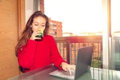 Фрилансер девушки работая с ноутбуком и выпивая напитком от стекла стоковое фото