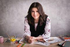 фрилансер: дизайнер женщины усмехается На настольном компьютере разбросанные эскизы, краски, щетки, образцы цвета и материал стоковая фотография