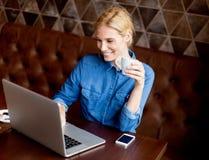 Фрилансер женщины работая на компьтер-книжке в кафе и выпивая кофе Стоковое Изображение RF