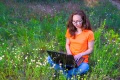 Фрилансер женщины работая на компьтер-книжке outdoors, удаленная работа Стоковая Фотография