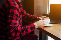 Фрилансер молодого человека наслаждается кофе в кафе используя компьтер-книжку Кофе работающий на самого себя работника выпивая и Стоковые Фотографии RF