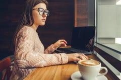 Фрилансер молодой женщины получает звонок в кафе используя компьтер-книжку стоковая фотография