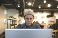 Фрилансер работает для компьтер-книжки в уютном кафе Молодой битник супруга использует компьютер в кафе для чашки кофе Стоковые Фотографии RF