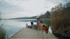 Фрилансер работает на его компьтер-книжке внешней рядом с озером, сидя на пруде сток-видео