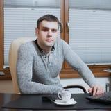 Фрилансер работника офиса сидит на столе и работе на компьтер-книжке во время перерыва на чашку кофе на офисе Стоковое Изображение