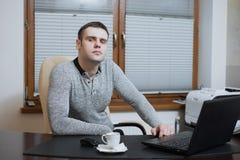 Фрилансер работника офиса сидит на столе и работе на компьтер-книжке во время перерыва на чашку кофе на офисе Стоковая Фотография