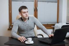 Фрилансер работника офиса сидит на столе и работе на компьтер-книжке во время перерыва на чашку кофе на офисе Стоковая Фотография RF
