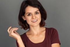 фристайл Молодая женщина изолированная на сером усмехаясь возбужденном конце-вверх стороны стоковое фото