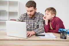 Фрилансер бизнесмена используя компьтер-книжку с сыном Стоковые Изображения