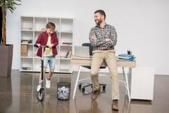 Фрилансер бизнесмена с сыном на самокате Стоковое Фото