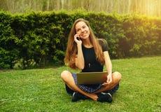 Фрилансер девушки работая outdoors с компьтер-книжкой и телефоном Стоковое фото RF