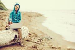 Фрилансер работая на тетради на побережье Стоковое Изображение RF