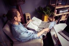 Фрилансер сидя в стуле кладя ноги на журнальный стол Стоковые Изображения RF