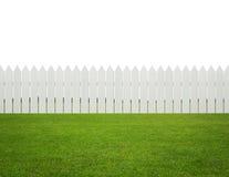 Фронт или задний двор, белая деревянная загородка на траве изолированной дальше