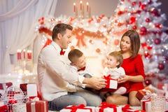 Фронт подарка семьи рождества открытый присутствующий дерева Xmas, счастливых детей матери отца стоковые фото
