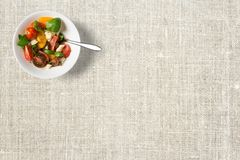 Фруктовый салат в белом шаре цвета с сияющей ложкой стоковая фотография