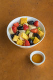 Фруктовый салат в белом шаре на оранжевой каменной предпосылке Стоковая Фотография