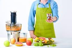 Фруктовый сок, пилюльки и дополнения витамина Женщина держа стеклянной вполне пилюлек стоя рядом с juicer с нагрузками свежих фру Стоковая Фотография RF