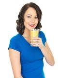 Фруктовый сок счастливой молодой женщины выпивая Стоковые Изображения