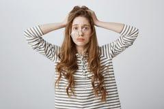 Фрустрация чувства девушки от невозможности зафиксировать проблему Портрет потревоженной и усиленной молодой женщины держа руки д стоковое изображение