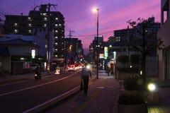 Фукуока, ЯПОНИЯ - 13-ое сентября 2017: Улица с людьми и автомобилями после захода солнца с розовым и фиолетовым небом Стоковая Фотография RF