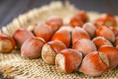 Фундуки грецкого ореха на мешковине на коричневом деревянном столе Стоковая Фотография RF