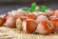 Фундуки грецкого ореха на мешковине на коричневом деревянном столе Стоковые Фотографии RF