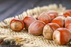Фундуки грецкого ореха на мешковине на коричневом деревянном столе Стоковые Изображения RF