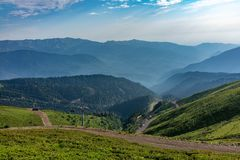 Фуникулер идет вниз от зеленого гребня Aibga Высокие горы в помохе на горизонте Krasnaya Polyana, Сочи стоковое изображение
